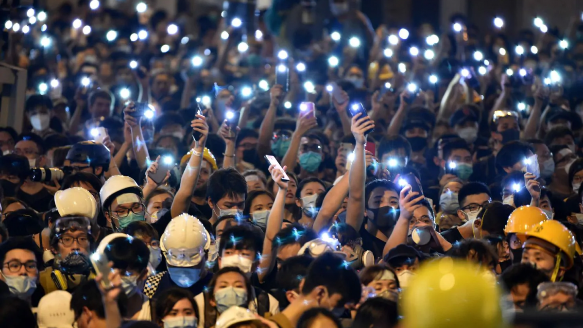 Protesters hold up their mobile phones as they gather outside the police headquarters in Hong Kong on June 21. (Hector Retamal/AFP/Getty Images)