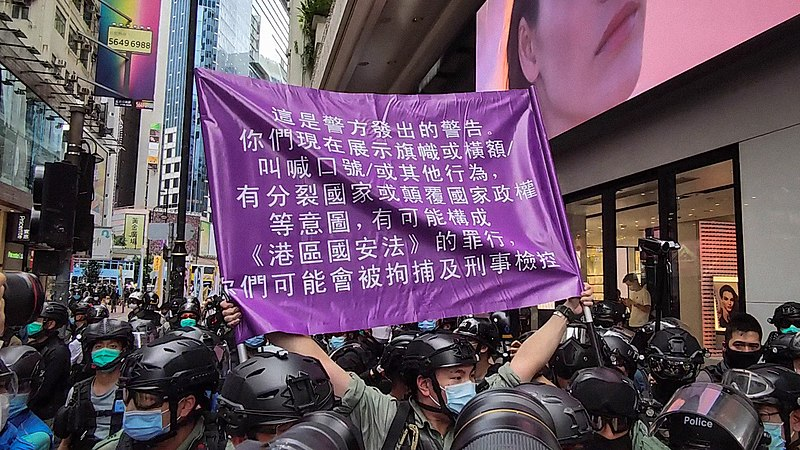 Police officer holds up a purple flag warning protestors against violations of the National Security Law